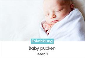 Ein Baby liegt eingewickelt auf einer Auflage