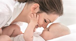 Eine Mutter und ihr kleines Baby liebkosen sich