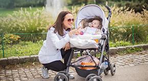 Mamma på promenad med barn i barnvagn