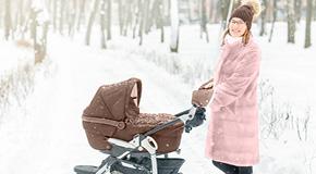Mamma med barnvagn i snö