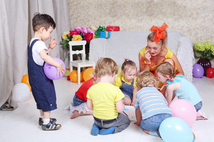 Kinder knien im Kreis und spielen zusammen