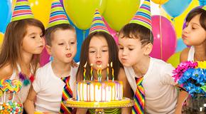 Kinder pusten gemeinsam einen Geburtstagskuchen