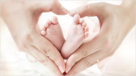 Mutter Hände umrahmen Babyfüßchen