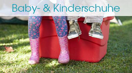 Zwei Kinder sitzen auf einer Kiste, die auf dem Rasen steht