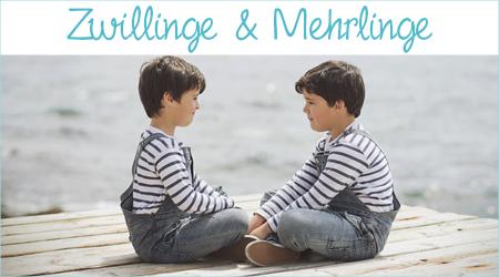 Zwei Zwillinge sitzen sich auf einem Steg gegenüber