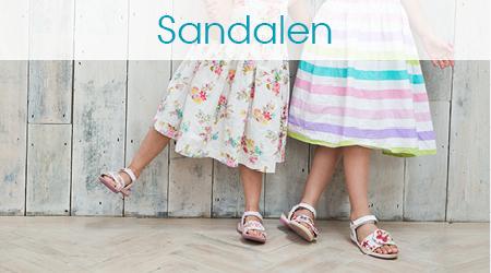 Zwei Mädchen in Kleidern und Sandalen