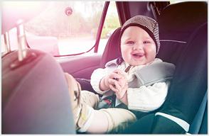 Lachendes Kind sitzt im Autositz