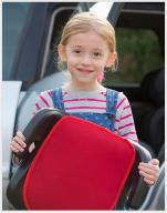 Mädchen steht mit Sitzerhöhung vor einem Auto
