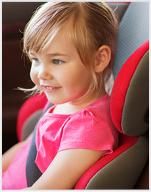 Lachendes Mädchen sitzt im Autositz