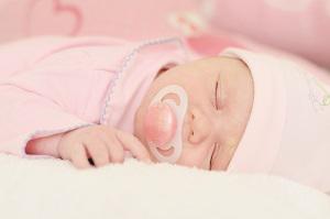 Baby in Schlafkleidung und Schnuller schläft ganz ruhig