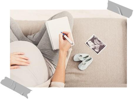 Schwangere mit Zettel und Stift auf der Couch sitzend. Neben ihr liegen Babyschuhe und ein Ultraschallbild
