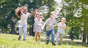 Kinder spielen draußen mit Seifenblasen