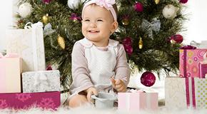 Kleines Mädchen sitzt vor einem Weihnachten und vielen Geschenken