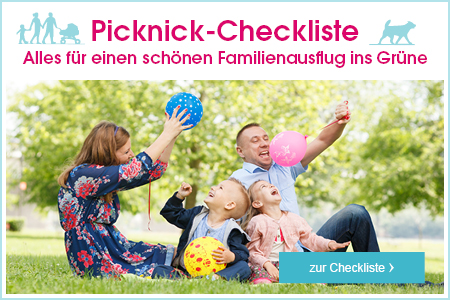 Familie sitzt im Park auf einer Decke und spielt