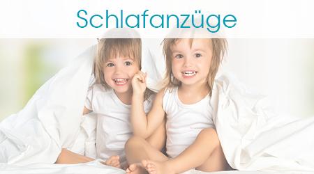 Zwei kleine Mädchen sitzen lächelnd und sind decken sich zu