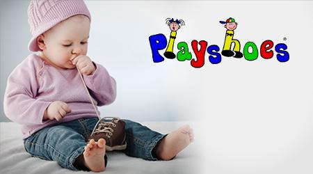 Ein Baby spielt mit einem kleinen Schuh