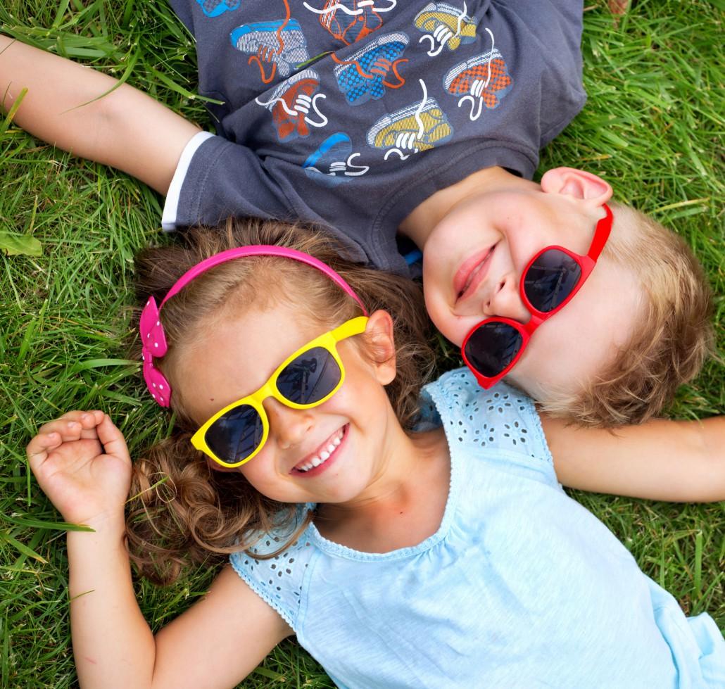 Mädchen und Junge liegen im Gras