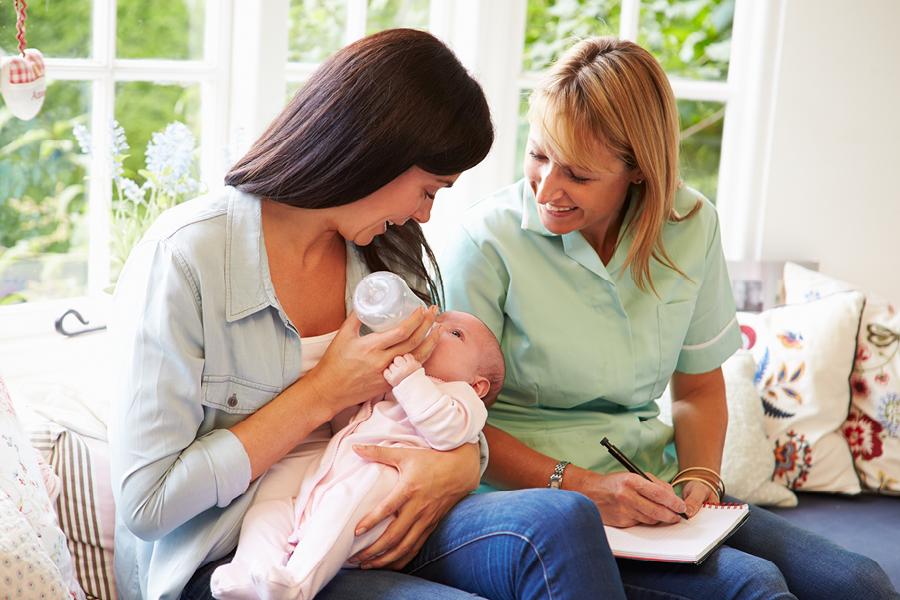 Frau füttert Baby, Hebamme schaut zu