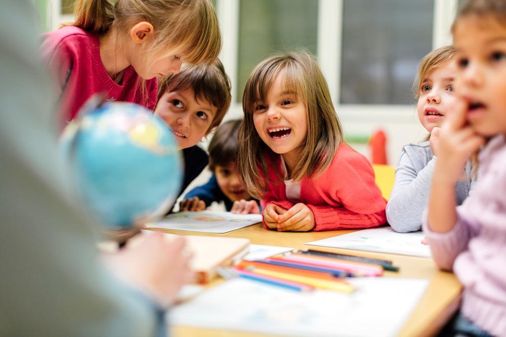 Kindergartenkinder malen gemeinsam am Tisch und lachen
