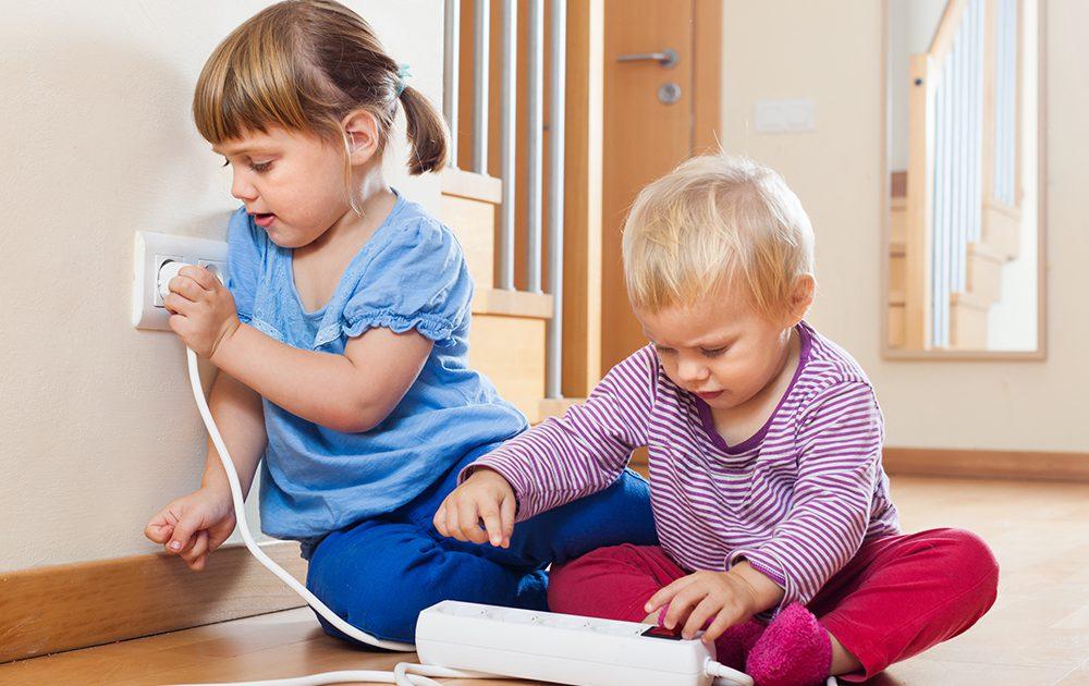 Zwei Kinder stecken eine Steckdosenleiste in die Steckdose
