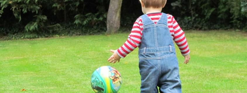 Kind spielt mit Ball im Garten