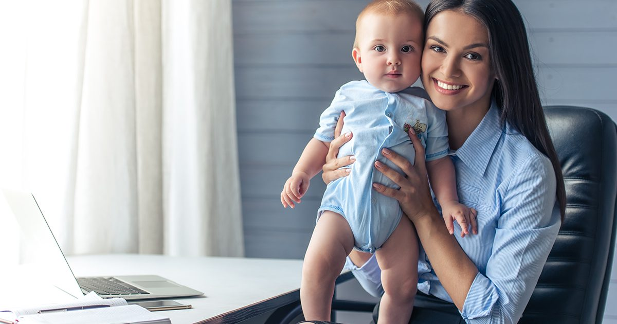 Frau im Businesslook mit Baby auf dem Schoß