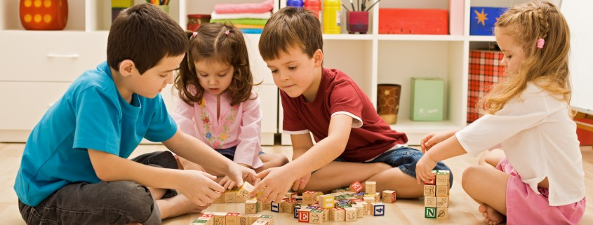 4 Kinder spielen Holz Klötzchen