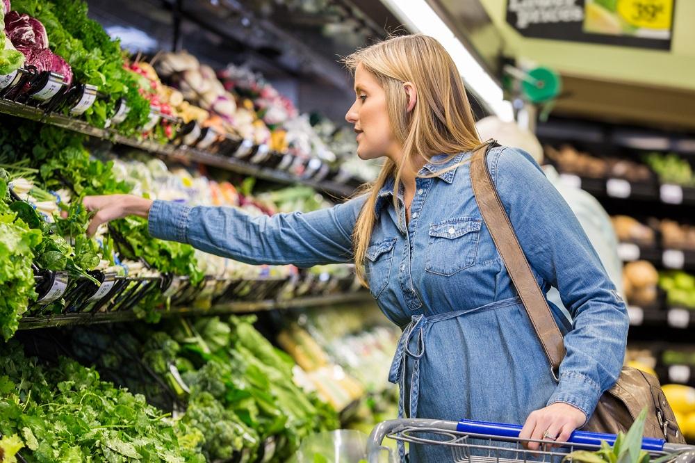 Schwangere steht im Supermarkt vor Gemüse-Regal