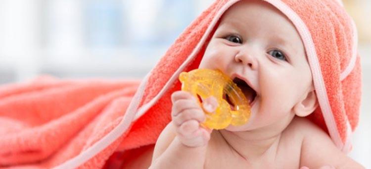 Baby im Handtuch mit Badespielzeug im Mund