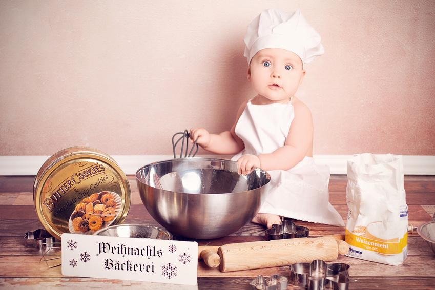 Baby mit Kochmütze backt Plätzchen