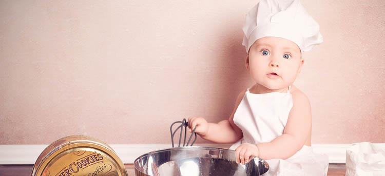 Baby mit Kochschüze will Plätzchen backen