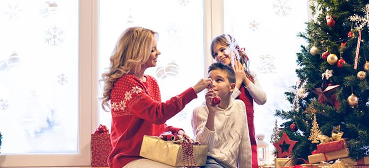 Mutter schmückt mit Kindern den Weihnachtsbaum