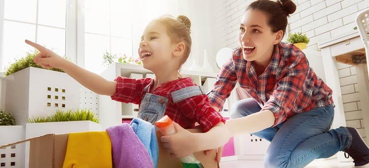 Mutter hilft Kind beim Aufräumen