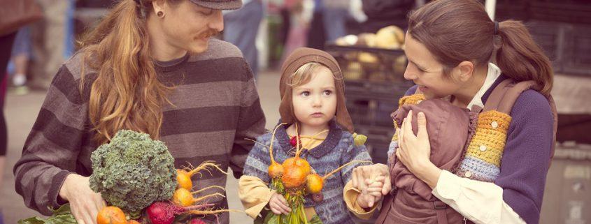 Familie mit Kleinkind kauft Gemüse auf dem Wochenmarkt.