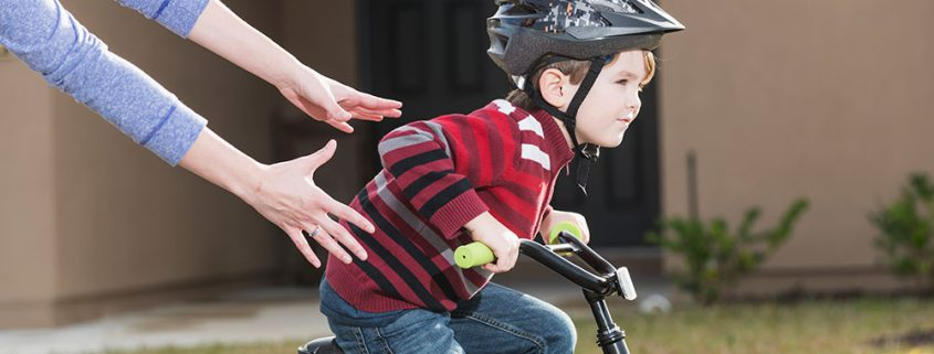 Eltern lassen Kind los damit es Fahrrad fährt