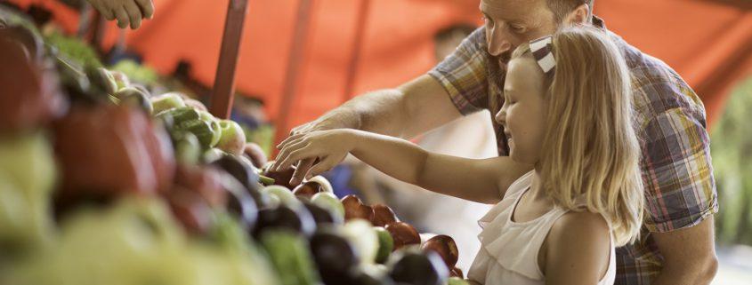Vater kauft mit Tochter Obst auf dem Markt