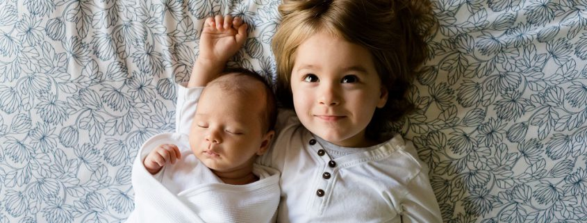 Geschwister liegen Arm in Arm
