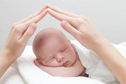 Hände der Mama beschützen schlafendes Baby