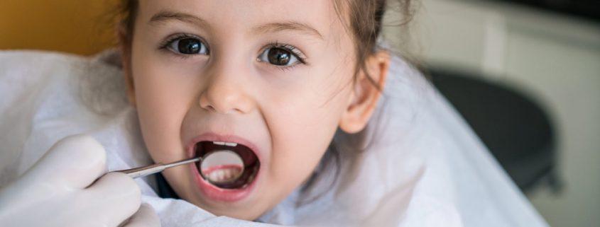 Kind beim Zahnarzt mit geöffnetem Mund wird untersucht