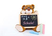 Teddybär hält Tafel mit Formel und Aufschrift Schule