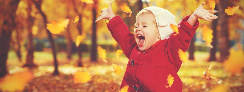 Kind spielt mit Herbstblättern