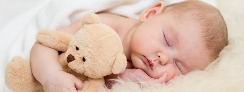 Neugeborenes schläft mit Kuscheltier im Arm