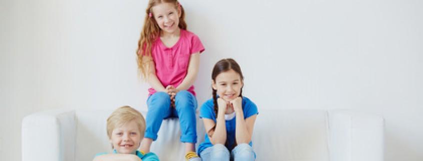 2 Mädchen und 1 Junge sitzen auf dem Sofa