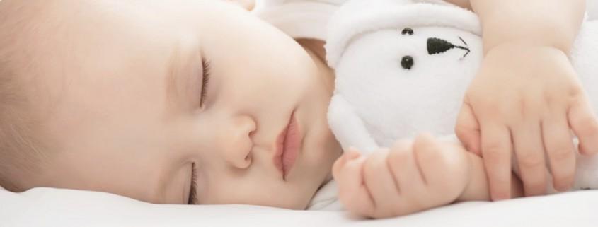 Baby schläft mit Teddy
