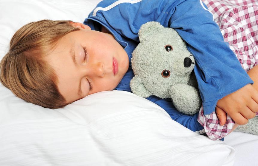 Kleiner Junge schläft mit Kuschelteddy