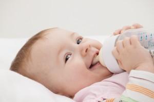 Lachendes Baby mit Fläschchen
