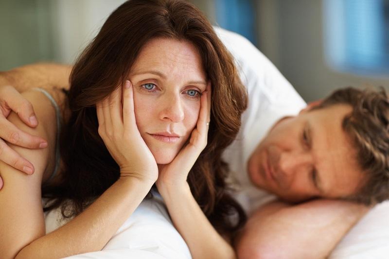 Paar liegt im Bett, Frau liegt auf dem Bauch und hat den Kopf sorgenvoll auf die Hände gestütz, Mann tröstet sie