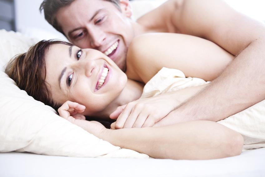 Paar liegt zugedeckt im Bett und lacht in die Kamera