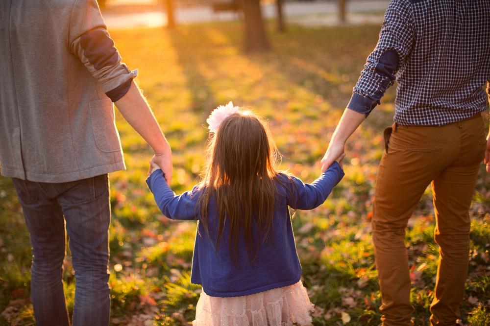 Zwei Väter gehen mit einem kleinen Mädchen spazieren