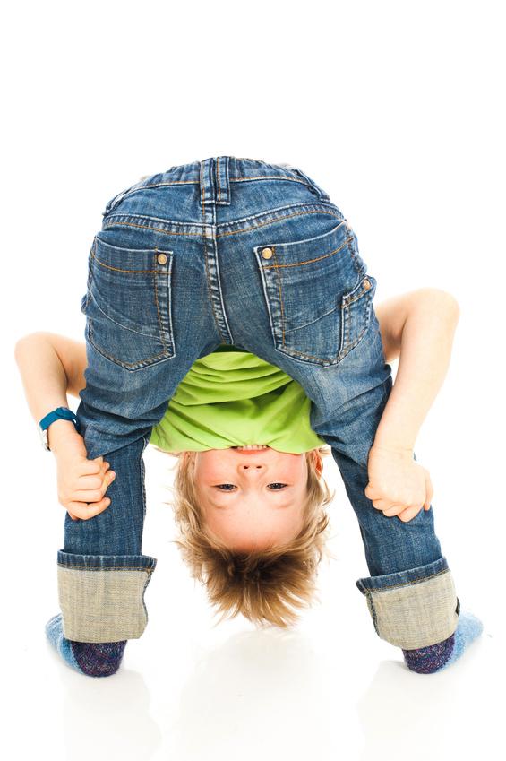 Kind hält seine Beine fest